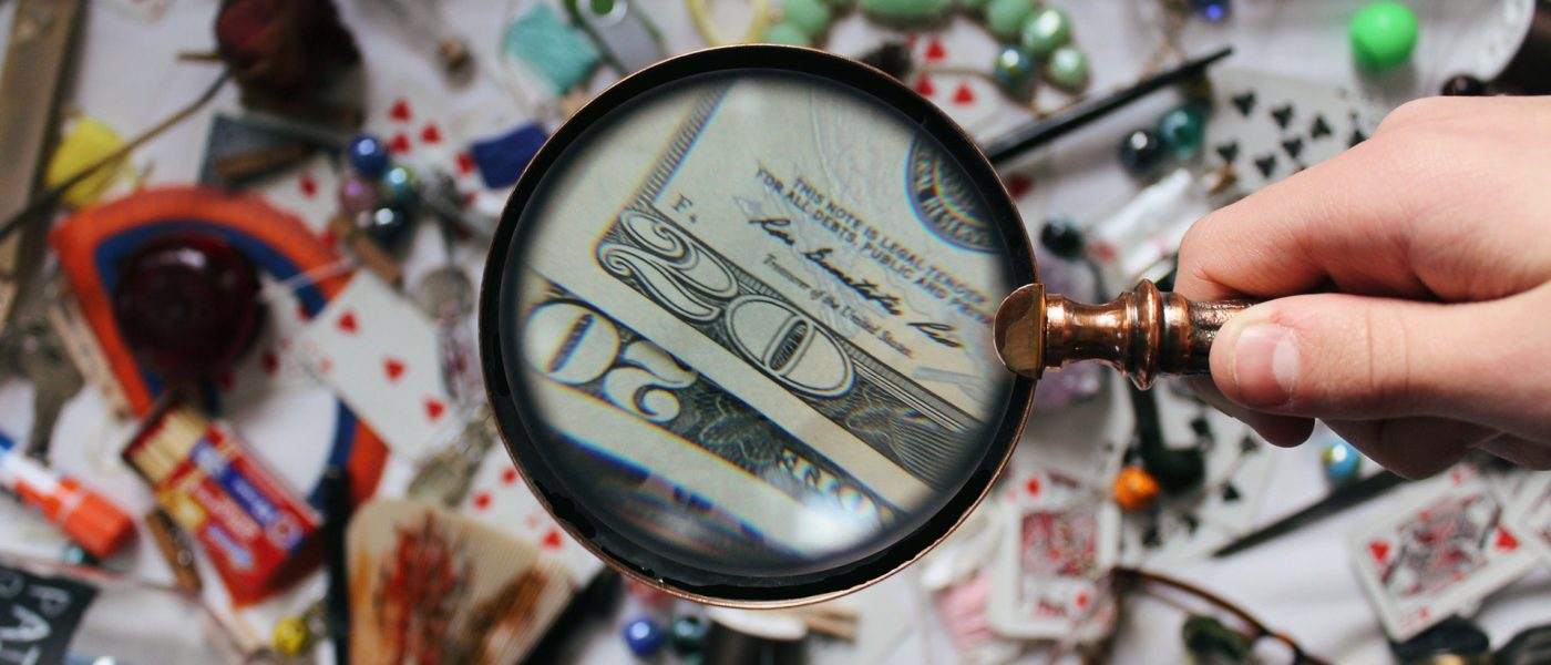 Magnifying glass spotting dollar bills amid a mess of objects