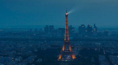 Eiffel Tower spotlight against a stormy evening sky