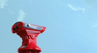 A red coin operated binocular against a bright blue sky